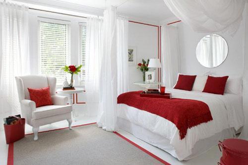 Белая спальня с красным одеялом и картинами на стене.
