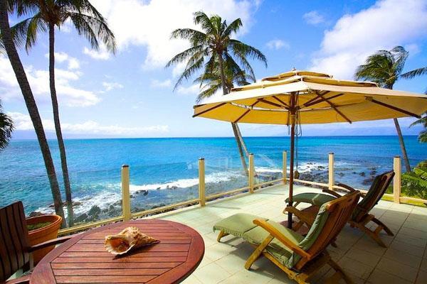 Тропический открытый зонтик, шезлонги, деревянный стол.