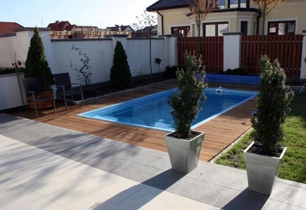 Прямоугольный бассейн в современном саду.