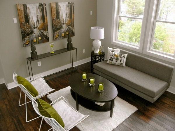 Стильный деревянный пол, серый диван, овальный журнальный столик.