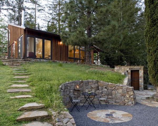 Стильный ландшафтный дизайн, каменная стена уличная мебель. Шикарная идея пейзажа с деревянной палубой и скамейками.