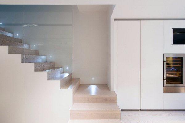 Лестница со стеклянными панелями ведет на второй этаж.