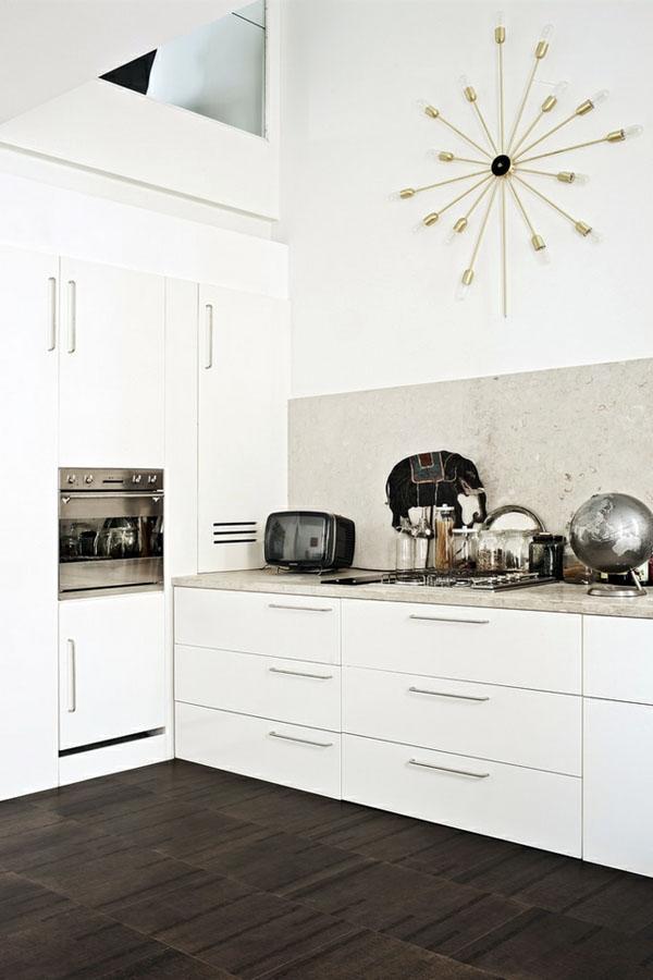 Темная напольная плитка в современной белой кухне.