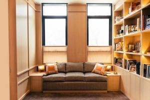 Интерьер дизайн диван настенные книжные полки светлые цвета…