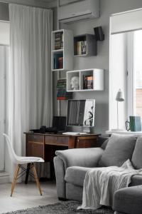 Серый диван деревянный стол стены книжная полка белый занавес